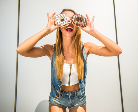 Photo for Playful young woman holding donuts against her eyes and smiling while standing against the wall. - Royalty Free Image