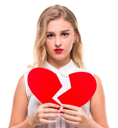 Foto de Young woman is holding a broken heart isolated on white background. - Imagen libre de derechos