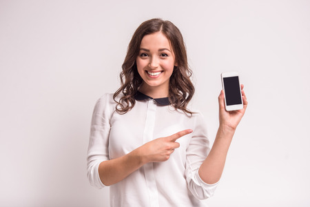 Photo pour Smiling woman is pointing on smartphone standing on white background. - image libre de droit