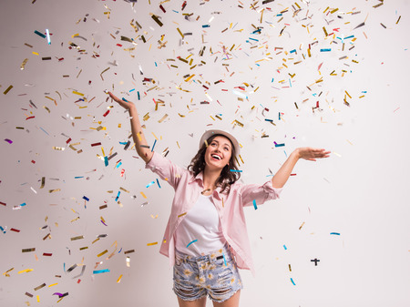 Foto de Cheerful young woman is stretching out her hands while confetti falling on her. - Imagen libre de derechos