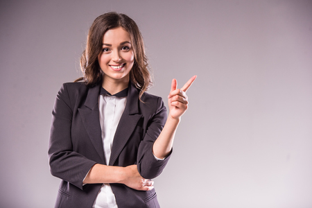 Foto de Smiling young woman is pointing at copy space over grey background. - Imagen libre de derechos