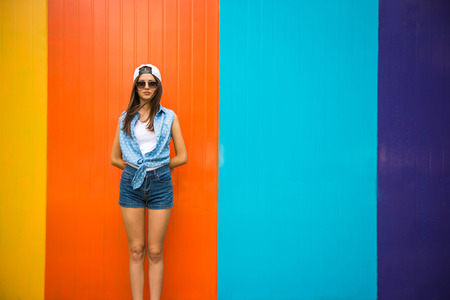 Photo pour Pretty cool girl in sunglasses and cap standing against the colorful wall. - image libre de droit