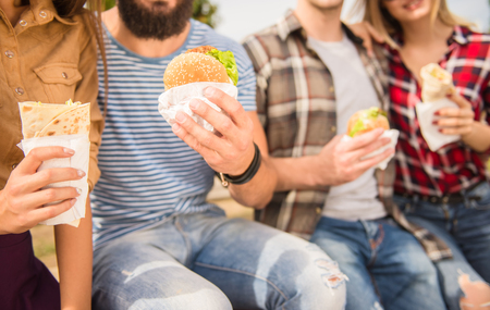 Photo for Young people walking outdoors. Sitting in the park and eat fast food - Royalty Free Image