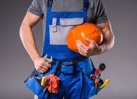 Foto de Construction work. Portrait of a young builder with tools in hand to build on gray background - Imagen libre de derechos