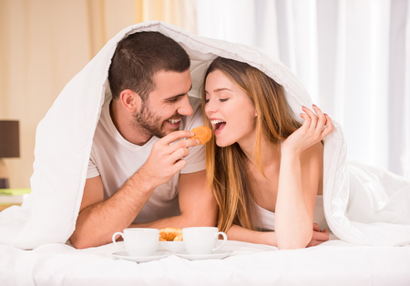 Photo pour Breakfast in bed. Young happy couple eating breakfast in her bedroom - image libre de droit