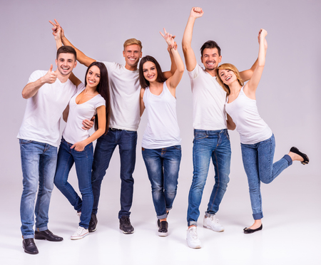 Photo pour A group of young people smiling on a gray background. Studio shooting - image libre de droit