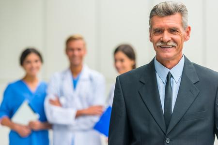 Photo pour Patron. Senior male businessman shakes hands doctors in hospital - image libre de droit