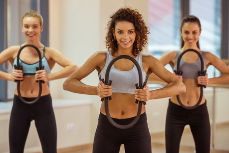 Photo pour Three attractive sport girls smiling while working out with pilates ring in fitness class - image libre de droit