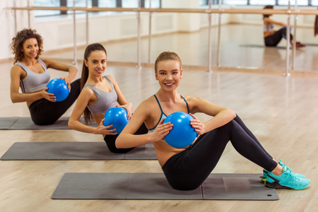 Photo pour Three attractive sport girls smiling while working out with fitness ball sitting on yoga mat in fitness class - image libre de droit