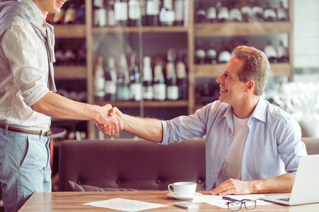 Photo for Handshake of two handsome businessmen in casual clothes meeting for working at the restaurant - Royalty Free Image