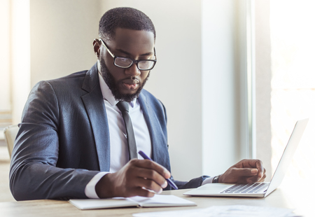 Foto de Handsome Afro American businessman in classic suit and eyeglasses is using a laptop and making notes while working in office - Imagen libre de derechos