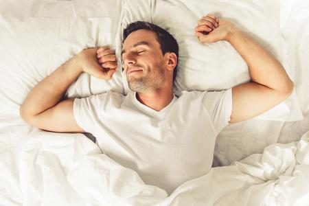 Foto de Top view of handsome man smiling while sleeping in his bed at home - Imagen libre de derechos