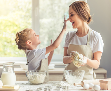 Foto de Cute little girl and her beautiful mom in aprons are playing and laughing while kneading the dough in the kitchen - Imagen libre de derechos