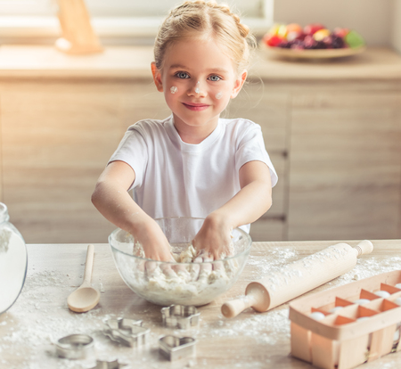 Photo for Cute little girl is looking at camera and smiling while kneading the dough in the kitchen - Royalty Free Image