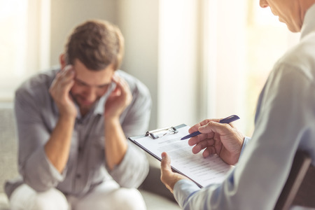 Foto de Handsome depressed man in casual clothes is leaning on his knees and telling about his problems while sitting on the couch at the psychotherapist. Doctor in focus - Imagen libre de derechos