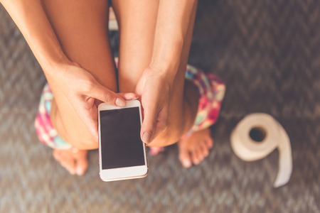 Photo pour Cropped image of beautiful young woman using a smartphone while sitting on toilet, close-up - image libre de droit