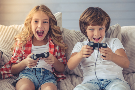 Photo pour Pretty little girl and boy are playing game console, looking at camera and smiling while sitting on sofa at home - image libre de droit