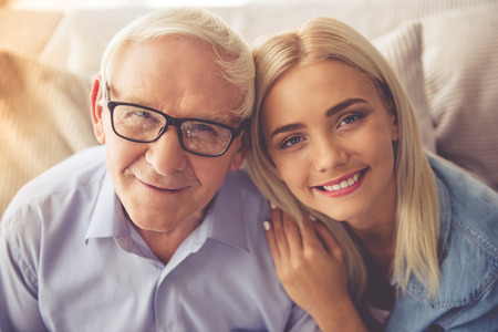 Photo for Portrait of handsome old man and beautiful young girl hugging, looking at camera and smiling - Royalty Free Image