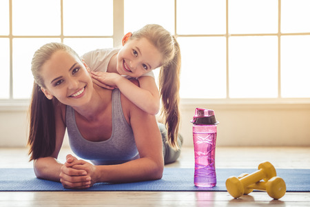Foto de Beautiful young woman and charming little girl are looking at camera and smiling while lying on yoga mat in fitness hall - Imagen libre de derechos