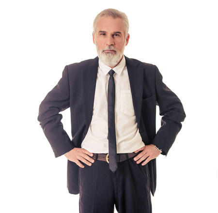 Photo pour Handsome bearded mature businessman in classic suit is looking at camera while standing akimbo on a white background - image libre de droit