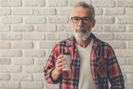 Foto de Handsome bearded mature businessman in casual clothes and eyeglasses is holding a cup of coffee and looking at camera, on a white brick wall background - Imagen libre de derechos