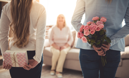 Foto de Teenage girl and her mom are hiding flowers and a gift box for their beautiful granny behind backs while grandma is sitting on couch at home - Imagen libre de derechos