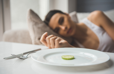 Foto de Suffering from anorexia. Slice of cucumber on the plate in the foreground, depressed girl lying in the background - Imagen libre de derechos