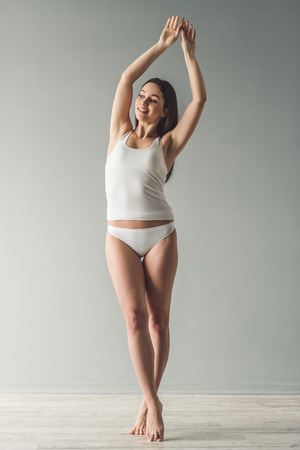 Full length portrait of attractive girl in white underwear smiling while standing on toes on gray background