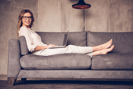 Beautiful business woman in casual clothes and eyeglasses is using a laptop, looking at camera and smiling while sitting on sofa at home