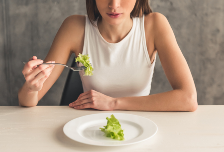 Photo pour Eating disorder. Cropped image of girl eating lettuce - image libre de droit