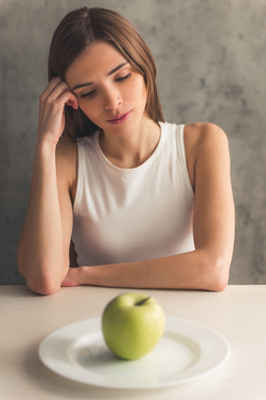 Foto de Eating disorder. Girl is sitting in front of the plate with an apple and looking at it - Imagen libre de derechos