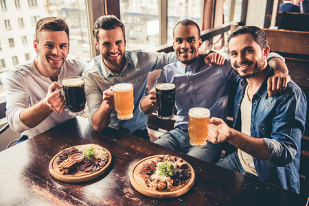 Handsome guys are drinking beer, looking at camera and smiling while resting in pub