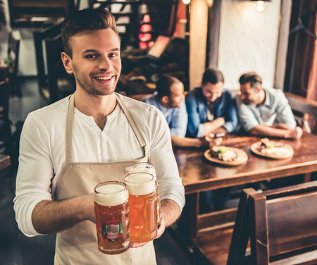 Handsome bartender in apron is holding beer, looking at camera and smiling while standing in pub