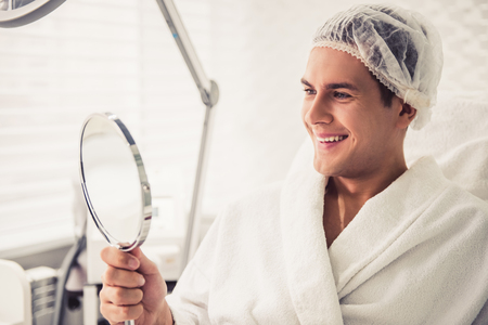 Photo for Handsome man is looking into the mirror and smiling while sitting at the cosmetician - Royalty Free Image
