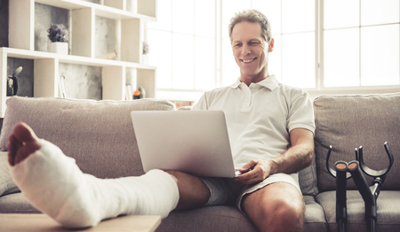 Foto de Handsome mature man with broken leg in gypsum is using a laptop and smiling while sitting on sofa at home - Imagen libre de derechos