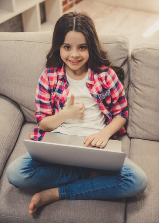 Photo pour Cute little girl in casual clothes is using a laptop, showing Ok sign and smiling while sitting on sofa at home - image libre de droit