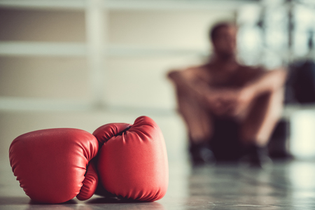 Photo pour Red boxing gloves in the foreground, boxer is sitting on the boxing ring in the background - image libre de droit