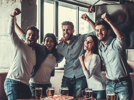 Foto de Victory! Group of young beautiful friends watching TV and cheering for their team while resting in pub. - Imagen libre de derechos