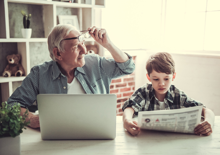 Foto de Grandpa and grandson resting at home. Handsome old man is using a laptop while his boy is reading a newspaper - Imagen libre de derechos