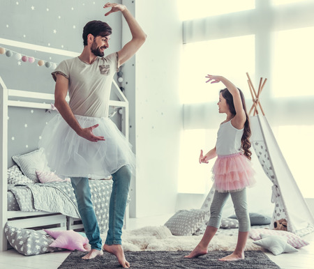 Photo for Cute little daughter and her handsome young dad in skirts are dancing and smiling while playing together in child's room - Royalty Free Image