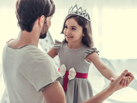 Foto de Cute little daughter and her handsome young dad are dancing and smiling while playing together in child's room - Imagen libre de derechos