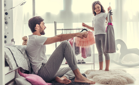 Foto de Cute little girl is showing her dad a beautiful holiday clothes and smiling while they are playing in her room - Imagen libre de derechos