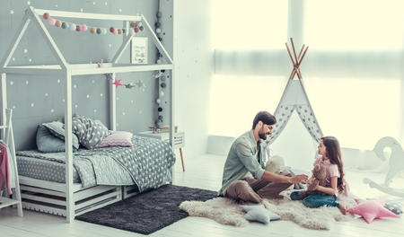 Foto de Cute little daughter and her handsome young dad are talking and smiling while playing together in child's room - Imagen libre de derechos