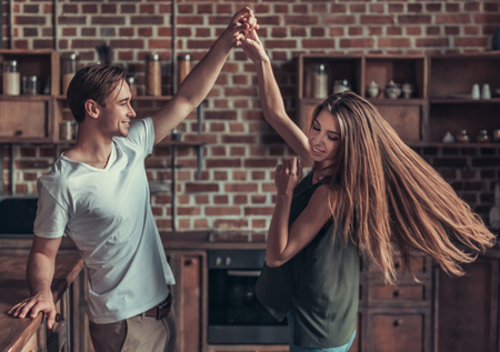 Photo pour Young happy couple dancing at home in the kitchen - image libre de droit