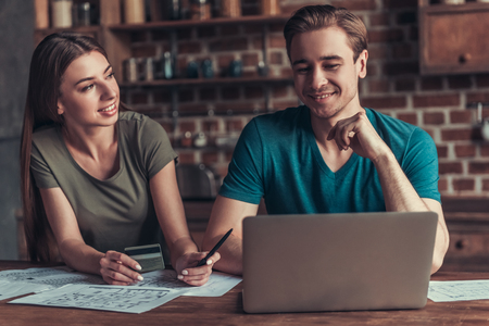 Foto de Family business. Young couple working with documents using laptop at home in the kitchen. - Imagen libre de derechos