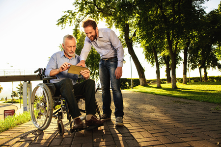 Foto de Old man in a wheelchair and a man looking at something in a tablet walking in the park. They are happy - Imagen libre de derechos