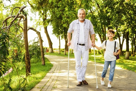 Foto de A boy and an old man on crutches are walking in the park. The boy is holding the old mans hand - Imagen libre de derechos