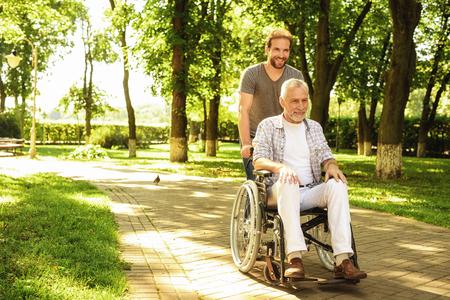Foto de A pensioner on a wheelchair and his adult son are walking around the park. They are happy and have fun - Imagen libre de derechos
