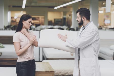 Foto de Orthopedic consultant helps a woman choose an orthopedic pillow. He shows her one of the pillow options - Imagen libre de derechos