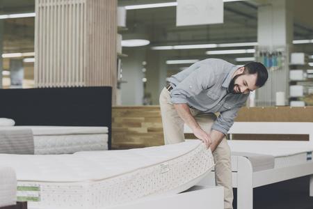 Foto de A man inspects a mattress in a mattress store. He lifted one of them - Imagen libre de derechos
